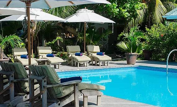 Liegen am Pool im 3-Sterne Plus Hotel Indian Ocean Lodge auf der Insel Praslin, Seychellen.