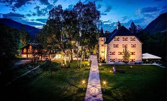 4-Sterne Hotel Schloss Prielau in Zell am See in Oesterreich. Zugang zum Schloss am Abend mit Beleuchtung.