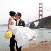 Brautpaar heiratet in San Francisco. Braeutigam hebt Braut hoch und kuesst sie vor der Golden Gate Bridge © MacDonald Photography