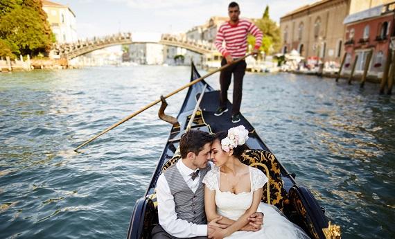 Verliebtes Brautpaar in einer Gondel mit Gondoliere in Venedig.