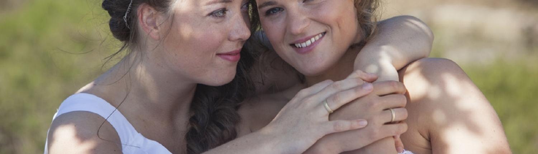Zwei lesbische Bräute lächeln und umarmen sich in der Natur an sonnigen Tagen.