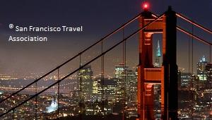 Die Golden Gate Bridge bei Nacht mit einem Tower in Nahaufnahme und der Skyline von San Francisco im Hintergrund.