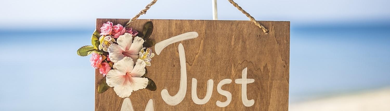 """Schriftzug """"just married"""" auf einem Schild mit Hibiskusblüten geschmückt"""