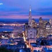 Beleuchtete Skyline von San Francisco von oben betrachtet im Hintergrund sieht man die beleuchtete Golden Gate Bridge.