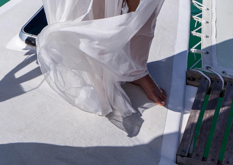 Braut auf dem Hochzeitskatamaran. Man kann nur den Fuss mit Perlenschmuck un dein Teil des Kleides erkennen..