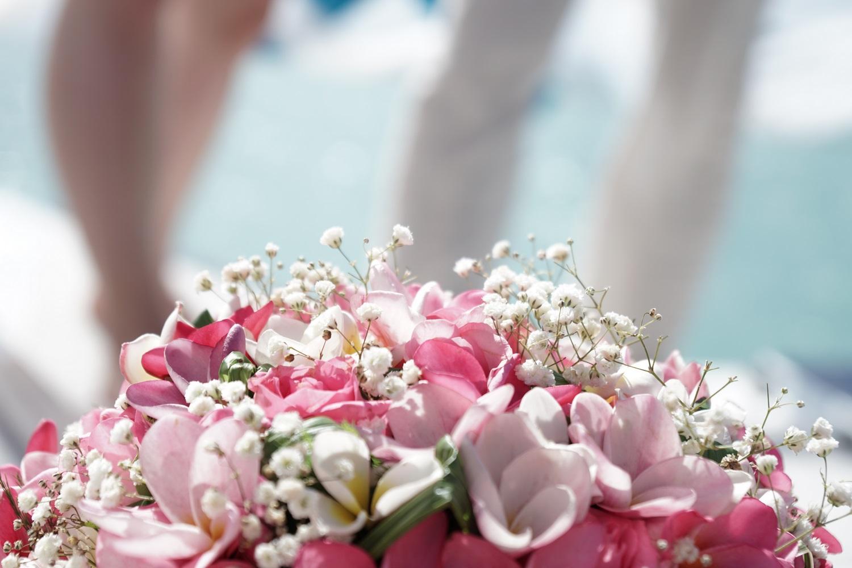 Grossaufnahme eines Braustrausses, man kann die Beine eines Brautpaars im Hintergrund verschwommen erkennen..